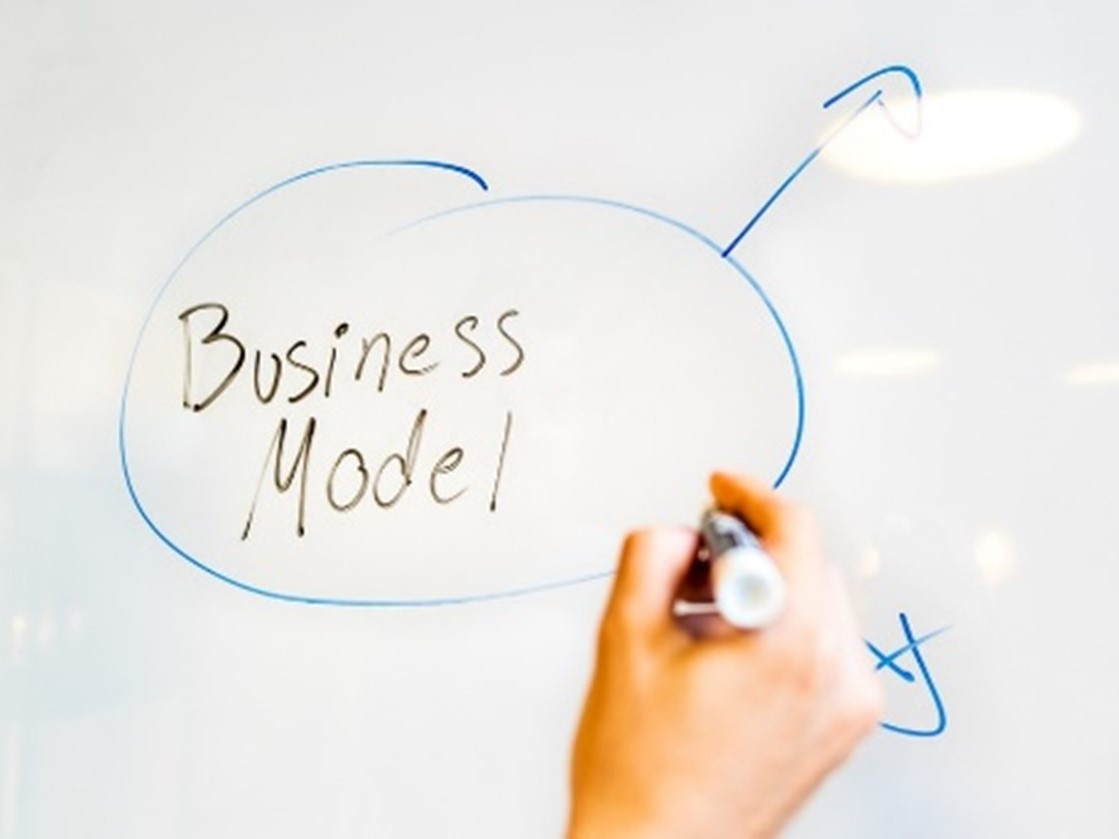 Someone writing business model on a whiteboard
